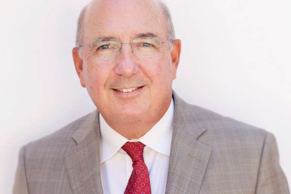 headshot of doctor Michael A. Dennis, a medical doctor. He is wearing a light grey patterned suit coat with a white collared shirt and a red and blue patterned tie. He is smiling and has very short grey hair and is wearing frameless glasses.
