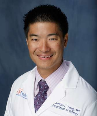 head shot of doctor Lawrence L. Yeung wearing a pinkish purple collared shirt with a dark purple tie with his white doctors coat. he has dark hair. the background of the photo is medium blue.
