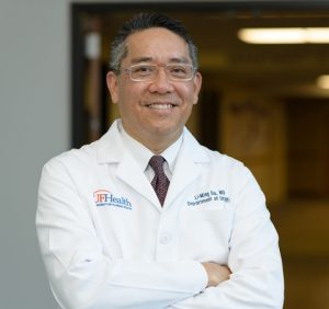head shot of doctor Li-Ming Su wearing his white doctor coat. He is standing with his arms folded across his chest. He is smiling. He is wearing a white shirt and a patterned tie. He is wearing glasses with a clear frame. he is standing in front of the department of urology sign located in the UF Health Shands Hospital North tower. This is the location of the administrative offices.