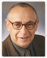 Head shot of Zev Wajsman Medical Doctor, Professor Emeritus Faculty. He is wearing a dark brown suit with a dark gray collared shirt and a gold tie with small dark designs. Doctor Wajsman is an older gentleman with dark gray balding hair and is wearing dark framed eyeglasses. The background of the photo is a light gray.