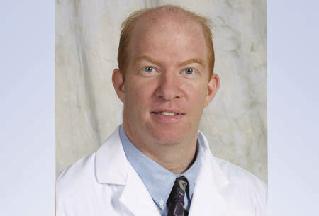 Head shot of doctor Vincent G. Bird is wearing his white doctors coat with a blue collared shirt and dark blue tie with gray and purple shapes.