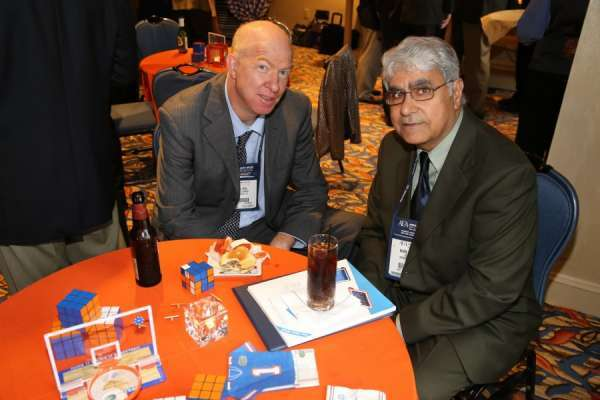 Doctors Bird and Kahn at the aua urogators alumni reception in 2013. Doctor Bird is wearing a dark suit with blue shirt and tie. Doctor Kahn is wearing a dark green suit with a mint green shirt and dark tie. They are seated at a table with a orange linen and gator items scattered on the top.