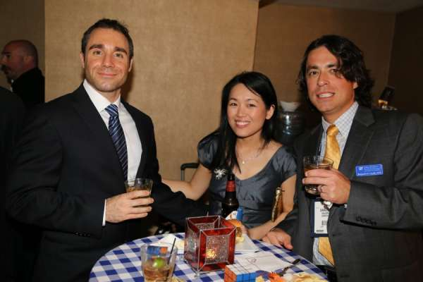 Doctors Kang and Calales with a guest at the aua urogators alumni reception in 2013. The guest is wearing a black suit with a white shirt and blue and black tie. Doctor Kang is wearing a gray cocktail dress. Doctor Canales is wearing a dark suit with a blue and white plain shirt and gold tie. In the background is the room the reception was held.