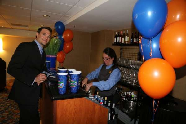 Doctor Evans and the bartender at the aua urogators alumni reception in 2013. He is wearing a dark suit with blue shirt and tie. The female bartender is wearing black pants and vest with a blue shirt. Orange and blue and balloons decorate the room.
