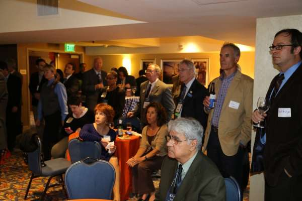 A large group of alumni, friends and colleagues at the aua urogators alumni reception in 2013. A mixture of male and female, all wearing business attire. They are listing to a guest speaker. In the background is the room the reception was held. Orange and blue linens and balloons decorate the room.