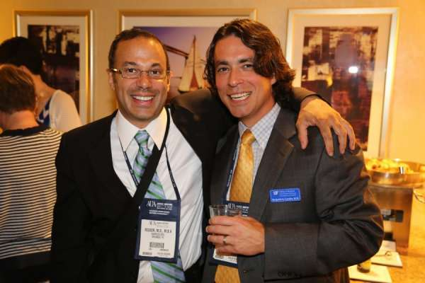 Doctors Rosser and Canales at the aua urogators alumni reception in 2013. Doctor Rosser is wearing a dark suit with a white shirt and blue, green and white tie. Doctor Canales is wearing a dark suit with a blue and white plain shirt and gold tie. In the background is the room the reception was held.