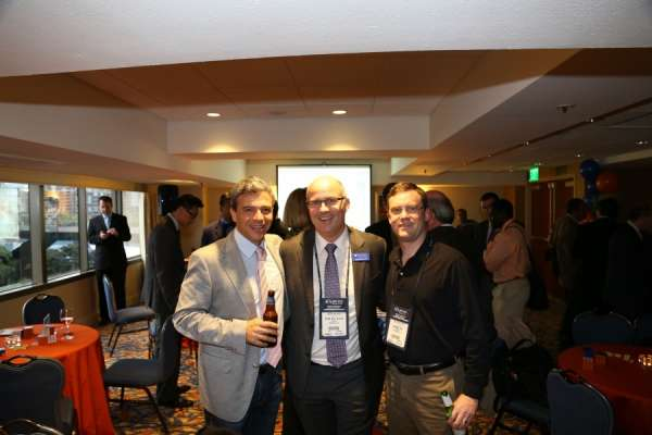 Doctor Philipp Dahm and 2 guests at the aua urogators alumni reception in 2013. Doctor Dahm is wearing a dark suit with white collared shirts and a purple and white tie. A male guest is wearing dark pants with a gray jacket, white shirt and pink tie. The other male guest is wearing tan pants and a black dress shirt. In the background is the room the reception was held. Orange and blue linens and balloons decorate the room.