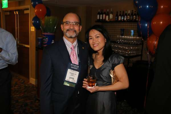 Doctor Kang and a guest at the aua urogators alumni reception in 2013. Doctor Kang is wearing a dark gray cocktail dress and holding a cocktail. Her guest is wearing a dark suit with a pink and white shirt and pink tie. In the background is the room the reception was held.