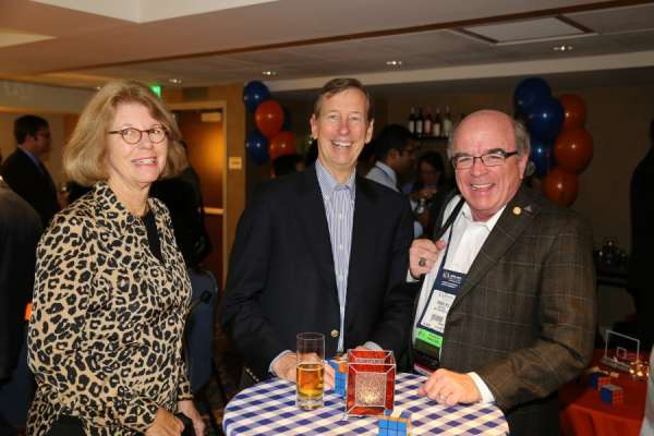Doctor Dineen and two guests at the aua urogators alumni reception in 2013. Doctor Dineen is wearing a dark brown suit with white shirt. His male guest is wearing a dark suit with a blue and white stripped shirt. His female guest is wearing a black shirt with a leopard print long sleeve jacket. Orange and blue linens and balloons decorate the room. People are laughing and smiling..