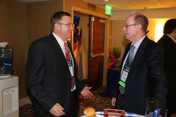 Doctor Crispen and alumnus doctor scott sellinger at the aua urogators alumni reception in 2013. Doctor Crispen is in a dark suit with shite collared shirt and red tie. Doctor Sellinger is in a dark blue suit with blue shirt and tie. In the background is the room the reception was held. Orange and blue linens with balloons decorate the room. People are laughing and smiling