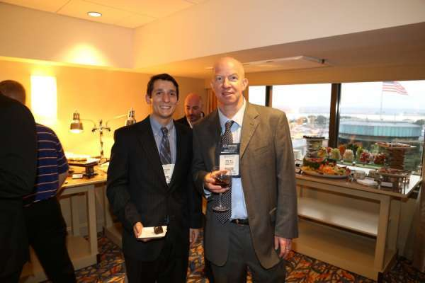 doctor bird and guest at the aua urogators alumni reception in 2013. Doctor bird is in a tan suit with white collared shirt and brown tie. His guest has on a dark suit with a blue shirt and tie. In the background is the room the reception was held in and shown are different food tables.