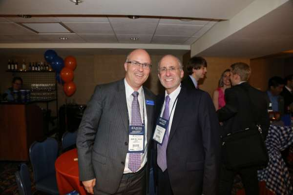 doctor dahm and guest at the aua urogators alumni reception in 2013. They are both in dark suits with white collared shirts and the same purple and white tie. In the background is the room the reception was held in. orange and blue linens and balloons decorate the room. people are laughing and smiling.
