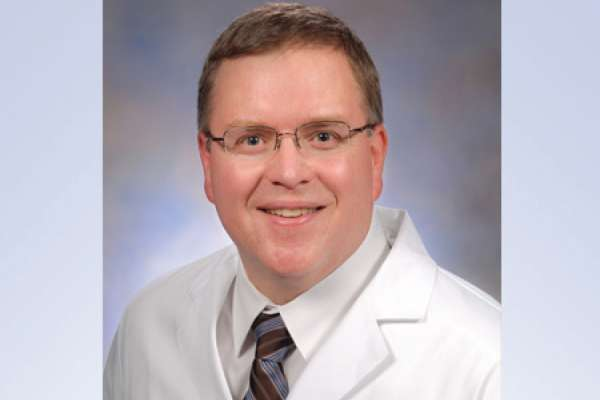 head shot of doctor Paul L. Crispen wearing a white doctors coat with a white shirt and blue and black striped tie. He is wearing clear framed glasses.