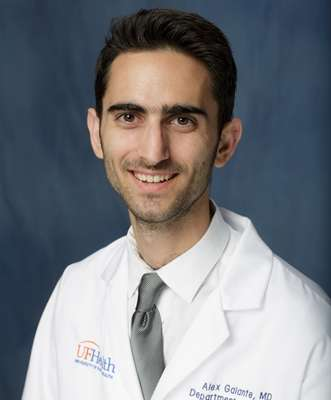 head shot of doctor Alexander Galante wearing a white doctors coat with a white collared shirt and grey tie