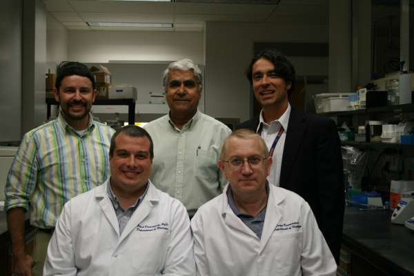 Picture of Dr. Canales and other doctors in a lab smiling at the camera