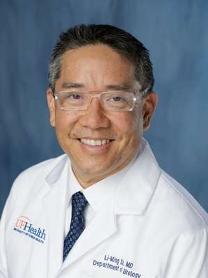 Photo of Doctor Li-Ming Su, a medical doctor. He is wearing his white doctors coat, white collared shirt and dark blue patterned tie. The background is a mix of dark and light blue color.