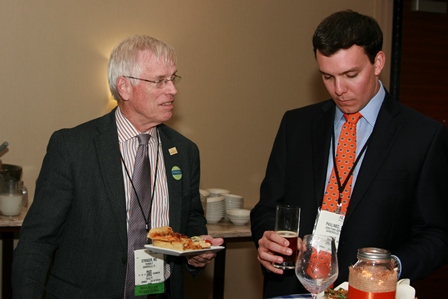 Photo of Doctor. Stringer a medical doctor standing with a resident doctor Pavlinec. Doctor Stringer is in a dark suit jacket with a white and light red striped collared shirt and lavender tie. Doctor Pavlinec is in a dark blue suit jacket with a light blue collared shirt and orange patterned tie. The background is of a coffee beverage table.