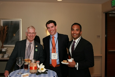 Small group photo of Doctor Stringer standing with two urology residents. Doctor Stringer is in a dark suit jacket with a white and light red striped collared shirt and lavender tie. One resident is in a dark blue suit jacket with a light blue collared shirt and orange patterned tie and the other resident is in a dark blue suit jacket with a white collared shirt and a dark tie. The background is of a coffee beverage table and a tan wall.