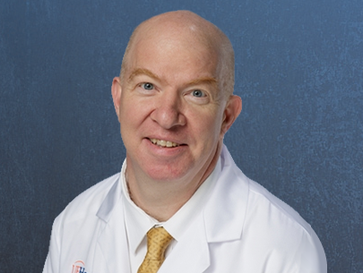head shot of doctor Vincent G. Bird is a medical doctor. He is wearing his white lab coat with a white collared shirt and a gold tie. He is balding. The background of the photo is medium blue.