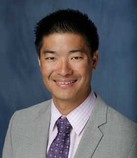 head shot of doctor Lawrence L. Yeung who is a medical doctor. He is wearing a grey suit coat a light pink and white checkered collared shirt and a purple, pink and white patterned tie. The background is a fading dark blue.
