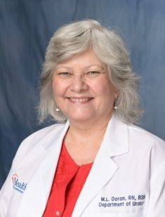 head shot of Michelle Doran, registered nurse, wearing a white doctors coat. she is wearing a red shirt. she is in her late 50's or early 60's. . she has shoulder length grey hair. the background of the photo is medium blue.
