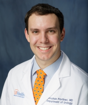 head shot of doctor Jonathan Pavlinec wearing a white doctor coat with a light blue shirt and orange tie with blue dots. He has dark hair. he is in his early 30's. the background of the photo is medium blue.