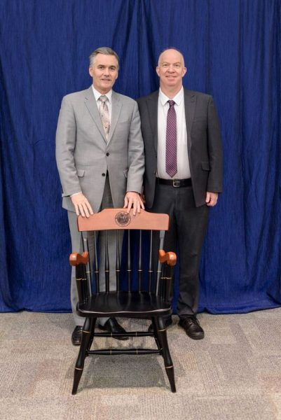 color photo of Dean Good presenting doctor Vincent G. Bird with his UF chair for the David A. Cofrin Endowed Chair in Endourology