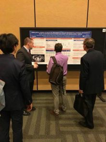 PICTURE OF PEOPLE LOOKING AT DR TERRY'S POSTER AT THE AUA