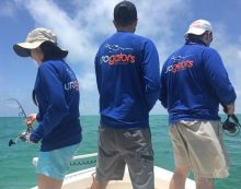 dr. wardenburg, dr vyas and dr. terry fishing off the back end of dr. su's boat