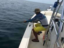 Dr. Yeung fishing off the side of Dr. Su's boat