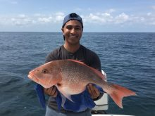 Dr Sharma holding his catch of the day - a large red fish