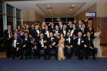 group pic of everyone doing the gator chomp at the resident graduation banquet