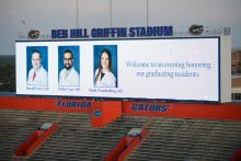 picture of the jumbotrons at the stadium with pics of dr. terry, vyas and wardenburg at the resident graduation banquet