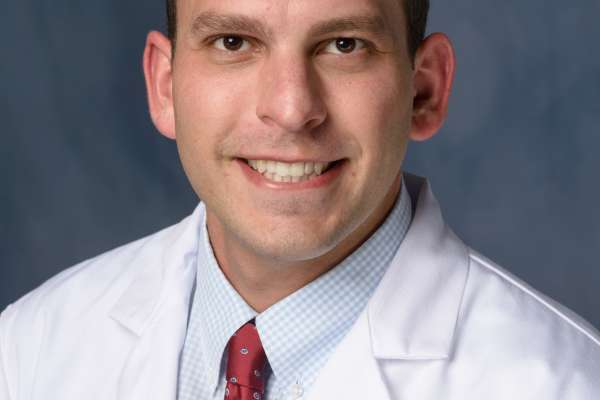 Kenan Ashouri, MD, Urology Resident, COM Urology, He is wearing a white doctors coat with a light blue checked shirt and a red tie with small designs.