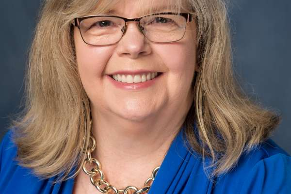 Photo of Stephanie Stenner, Resident Coordinator for the University of Florida Department of Urology. She is smiling and is wearing a blue blouse, she has shoulder length blonde hair and has on brown framed glasses.