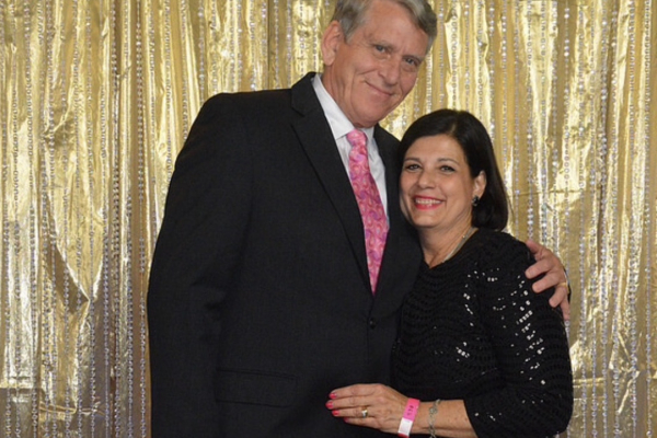 picture of chris maxfield and his wife standing in front of a gold lame curtain. they have their arms around each other. Chris is wearing black suit, white collared shirt and pink tie. His wife has on a back cocktail dress.