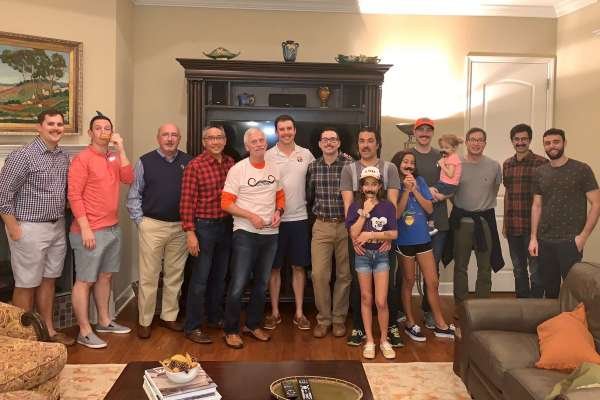 Group photo of some UF Urology faculty and their family. Some are holding a paper cutout of a black mustache under their noses