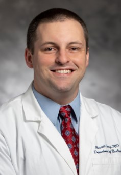 Photo of doctor russell terry who is a medical doctor in his white lab coat, light blue collared shirt and red and light blue patterned tie. Doctor Terry is smiling and there is a grey background behind him.