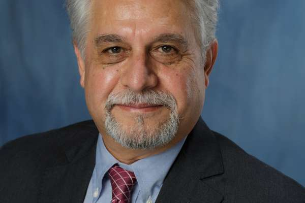 Doctor Vafa headshot. He is wearing a dark blue suit, light blue shirt and red tie. He has gray hair and a grayish mustache and goatee
