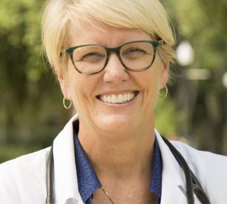 She is wearing a white doctors coat with a stethoscope around her neck. She has short blonde hair and she is wearing glasses. The background is a faded green.