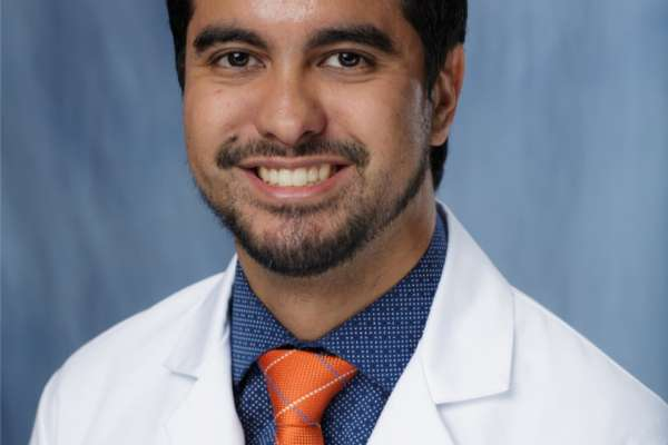 doctor grajo is wearing a white doctors coat. he has on a dark blue collared shirt and a orange tie. He is in his 30's. He has dark hair and dark facial hair. The background of the photo is medium blue.