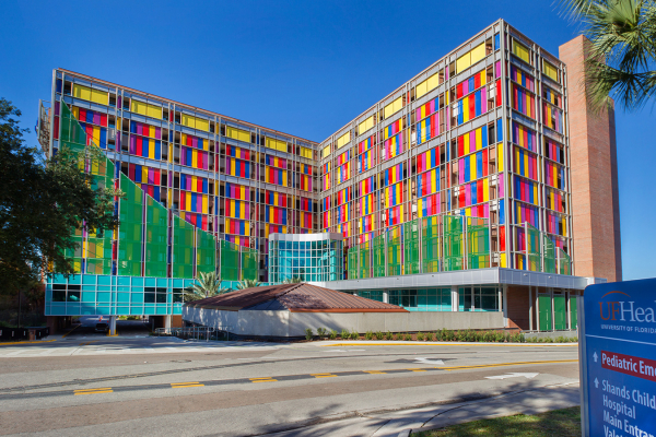 Photo of University of Florida Health Shands Children's Hospital which is a very tall building the alternating colored windows in yellow, red, blue and pink.