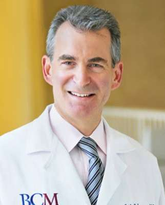 Doctor seth P lerner is the visiting professor for 2020 for uf urology. he is wearing a light colored shirt with a multi-striped tie. He is wearing his white doctors coat.