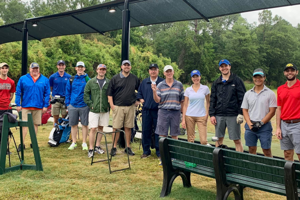 faculty and residents at the golf tournament. the are standing in a line and are all wearing casual golfing clothes.