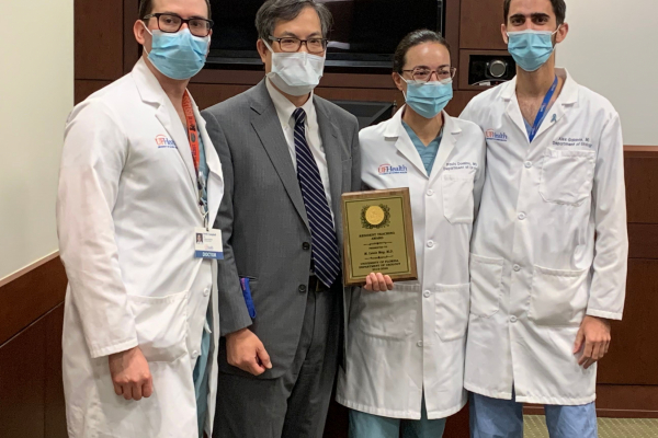 Doctors campbell, moy, domino and galante after presenting an award to doctor moy. doctor campbell is wearing scrubs with a white doctors coat. doctor moy is wearing a grey suit with a white collared shirt and dark blue striped tie. he is holding an 8 x 10 wooden plaque with gold plate. doctor domino is wearing scrubs and her white doctors coat. doctor galante is wearing scrubs and a white doctors coat.