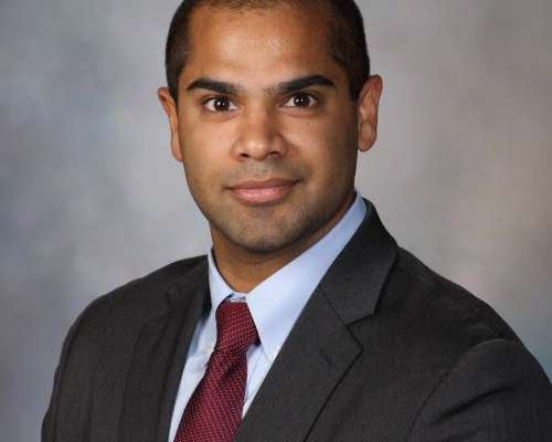 doctor joseph wearing a dark grey suit, light blue collared shirt and maroon tie. the background of the photo is blue and grey.