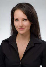 doctor schmidt is wearing a black dress. she has long dark hair. the background is a light blue.