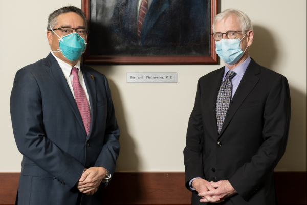 DOCTORS SU AND STRINGER IN THE UROLOGY CONFERENCE ROOM. THE ARE STANDING IN FRONT OF AN OIL PORTRAIT OF DOCTOR BIRDWELL FINLAYSON. DOCTOR SU IS WEARING A DARK BLUE SUIT WITH A WHITE COLLARED SHIRT AND PINK TIE. HE IS WEARING A FACE MASK. DOCTOR STRINGER IS WEARING A DARK BLUE SUIT WITH A PURPLE COLLARED SHIRT AND PURPLE AND GRAY TIE.