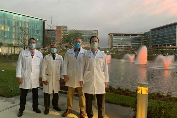 group picture from left to right, Dr. Li-Ming Su, Dr. Brian Ramnaraign, Dr. Paul Crispen & Dr. Padraic O'Malley. They are all wearing white doctors coats with dress shirts, ties and dress pants. they all having on face masks. they are standing in front of 5 water feature fountains that are colored orange. in the background is the hotel eleo, the uf health cancer hospital and the uf neuromedicine hospital.
