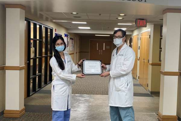 doctor jenny kuo is being presented a certificate from doctor lou moy. they are both wearing white doctor coats and face masks. they are standing in the department of urology hallway